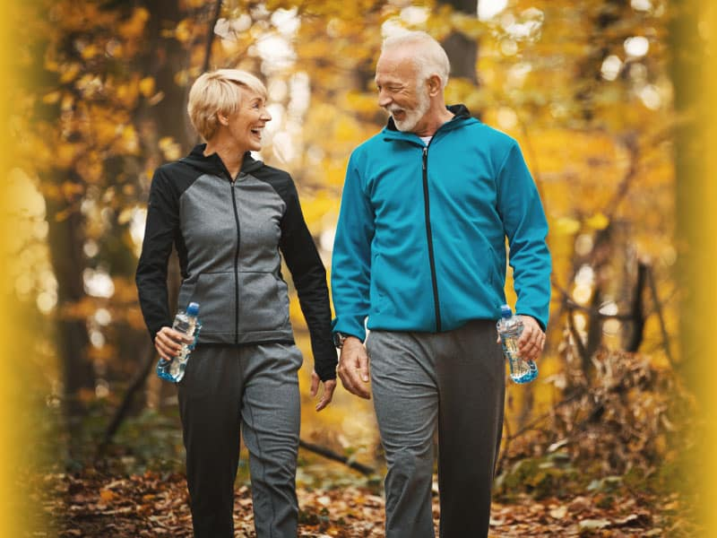older couple walking in forest