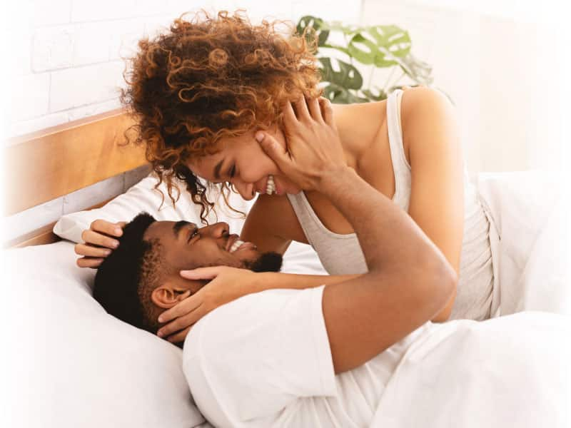 couple smiling at each other in bed