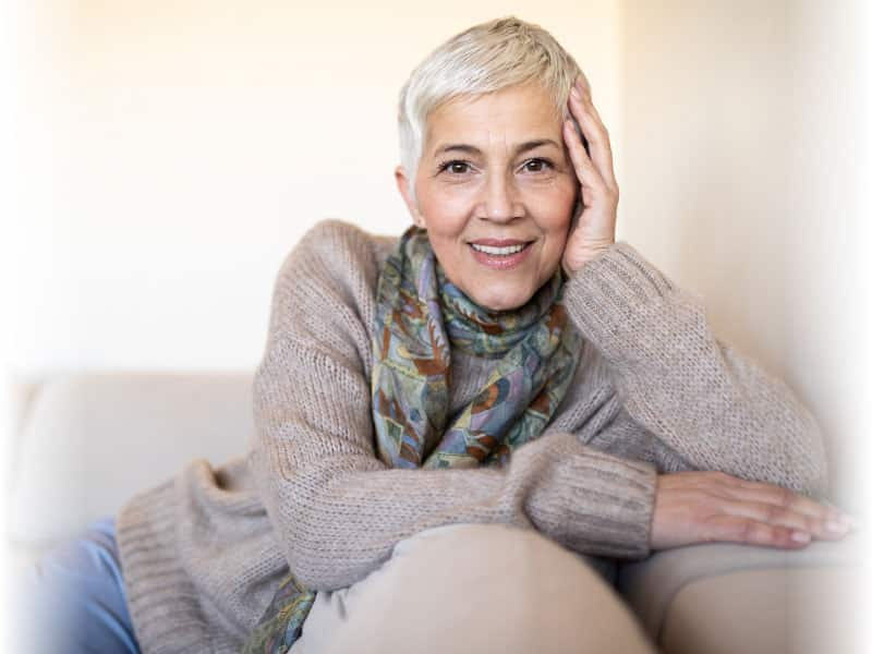 older woman smiling on a couch
