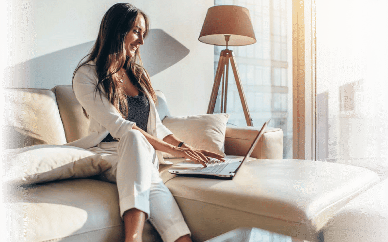 woman working from home on a laptop sitting on couch